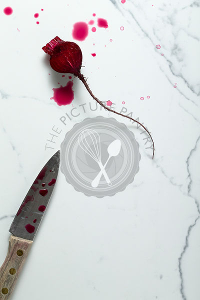 Washed and cut half baby beetroot on a marble tile surface, with a knife and juice splashes.