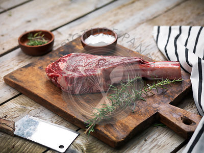 Raw fresh angus meat tomahawk on a wooden cutting board with rosemary, salt and butcher's knife