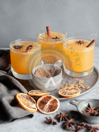 Three glasses of an orange spiced drink on a grey background, garnished with cinnamon sticks, brown sugar, blood oranges, and...