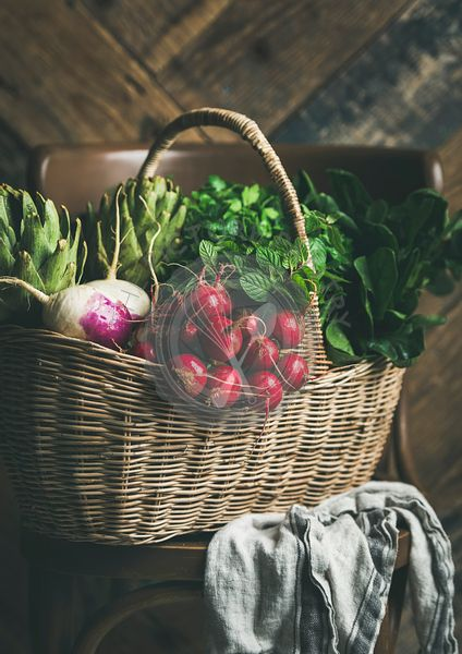 Basket of fresh organic garden vegetables and greens on chair