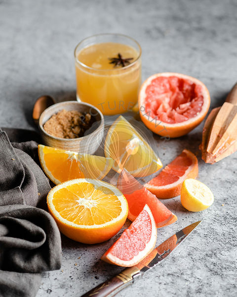 Sliced and halved oranges and grapefruits on a grey marble countertop, surrounded by a wooden hand juicer, a pocket knife, a ...