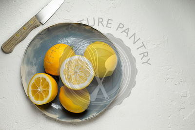 Fresh lemons, whole and sliced in half, arranged on a blue hand made plate. A wooden handled knife is alongside.