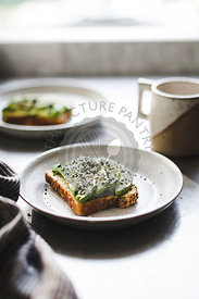 Sliced avocado and sesame seeds on seeded toast