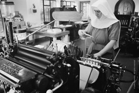 One of the Sisters operating the print machine in the printworks at Ladywell Convent, Godalming, the Motherhouse of an Intern...