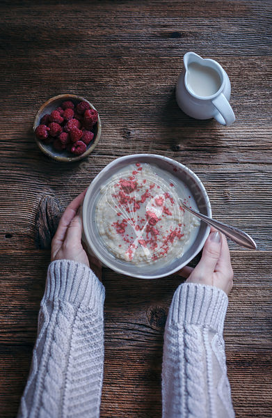 Woman eating millet porridge with raspberry powder