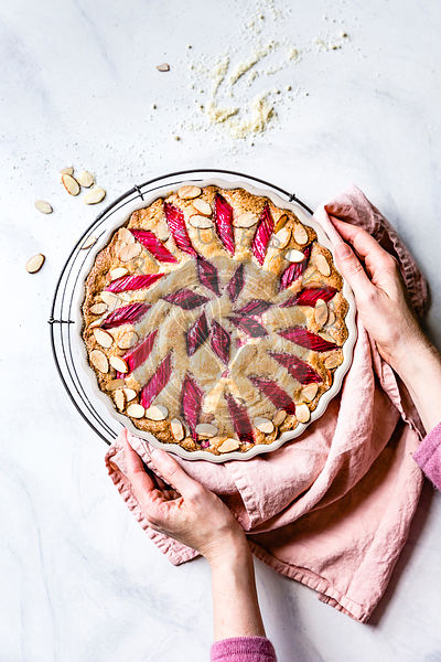 Rhubarb cake in a hand held baking dish being placed on a cooling rack.