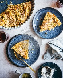 An Egyptian Phyllo Milk Pie (Um Ali) plated on blue dishes, served with coffee and garnishes of pistachio and confectioner's ...