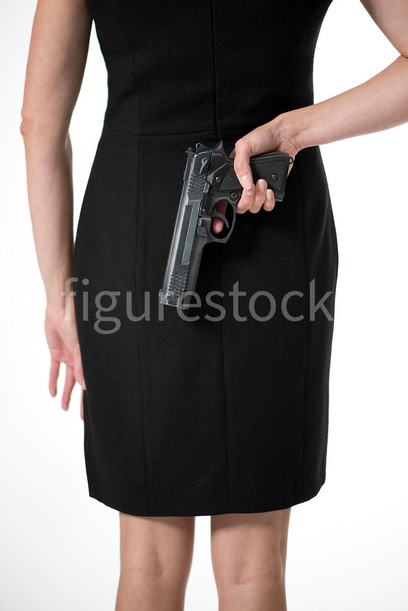 A woman standing with a gun behind her back – shot from mid level.