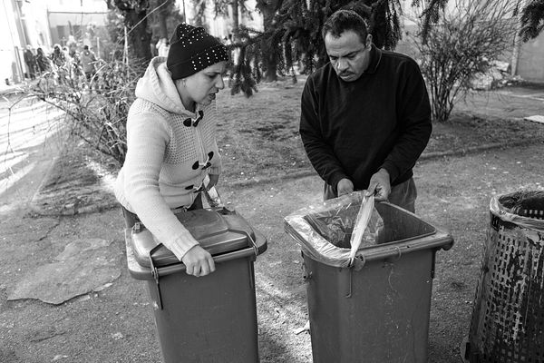 Shima and Yasser setting the garbage and recycling bins in the clean courtyard. The families were advised to organize among t...
