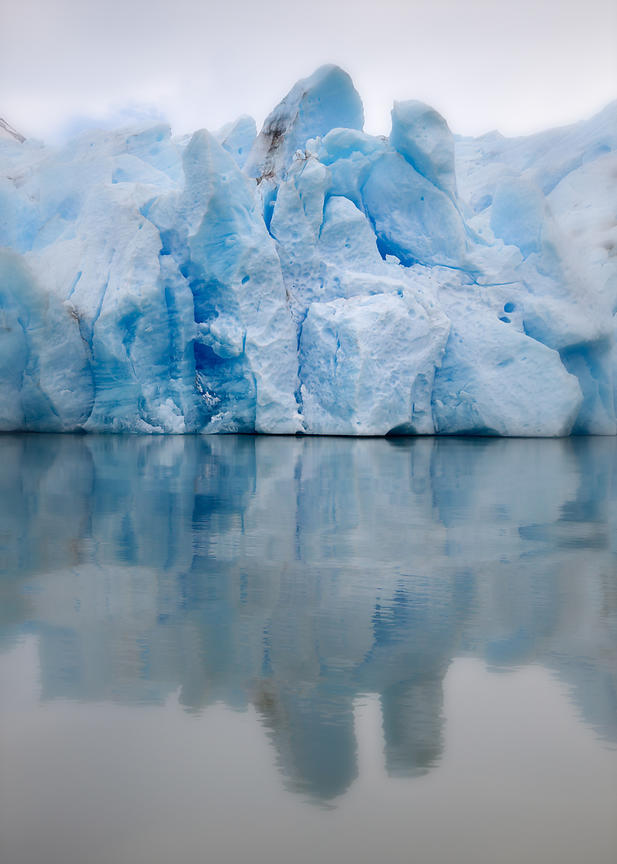 Detail of the blue ice of Glacier Grey on the border of its glacial lagoon, Lago Grey, and its reflection in the water.