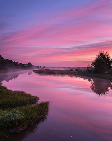 Dawn sky and rising mist from a mirror calm River Clyst at Topsham, Devon, UK