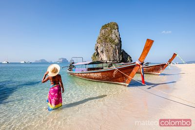 Woman at the beach near longtail boats, Railay, Thailand