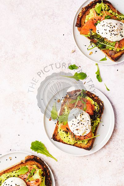 3 smoked salmon toasts with avocado cream, poached eggs and sesam seeds on top, with space for text.