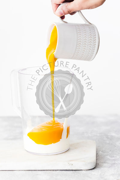 Lady pouring Mango Pulp to the Blender Jug