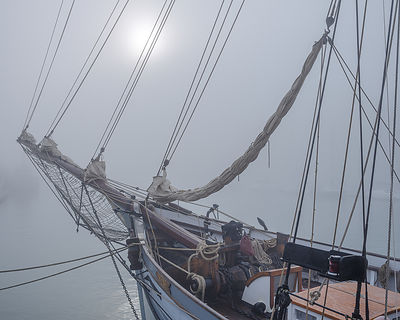 Sun breaking through fog with traditional ketch 'Irene' in  Weymouth Harbour, Dorset, UK