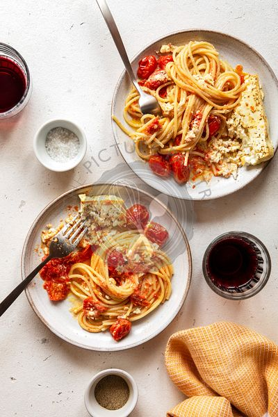 Two plates with baked feta cheese and tomato spaghetti on a table