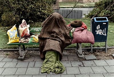 Homeless person with head covered by a sleeping bag sitting on a bench.