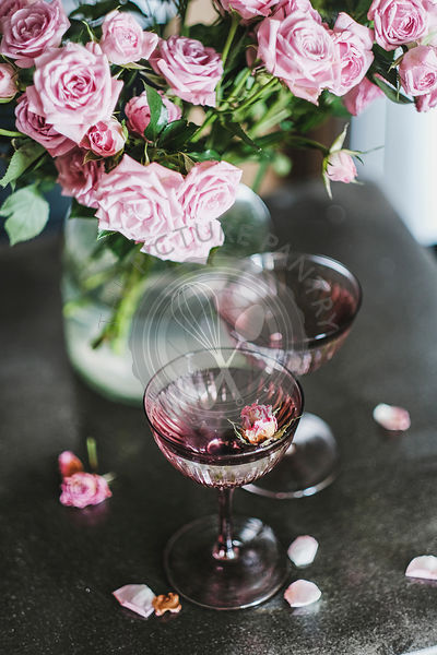 Champagne in glasses and tender pink roses bouquet in vase