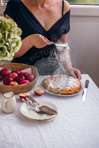 Woman dusting apple cake with powder sugar