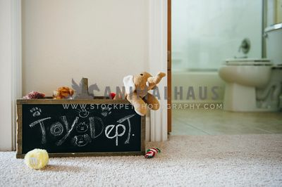 A chalk labelled toybox with stuffed animals and toys spilling out of it.