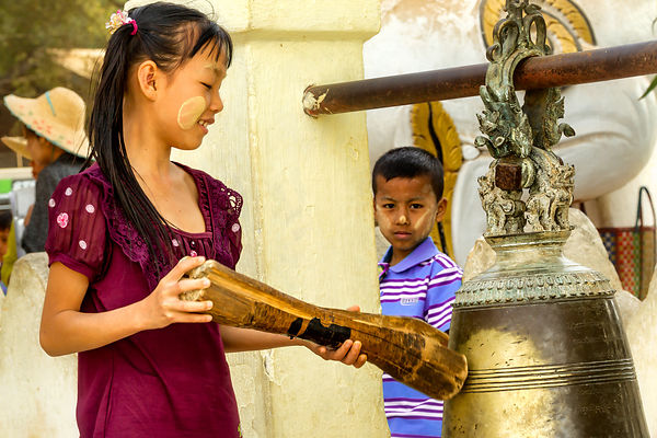 Girl Hitting the Bell at Bupaya Pagoda