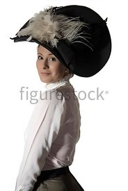 An Edwardian woman in a big hat, standing and looking at camera – shot from eye-level.