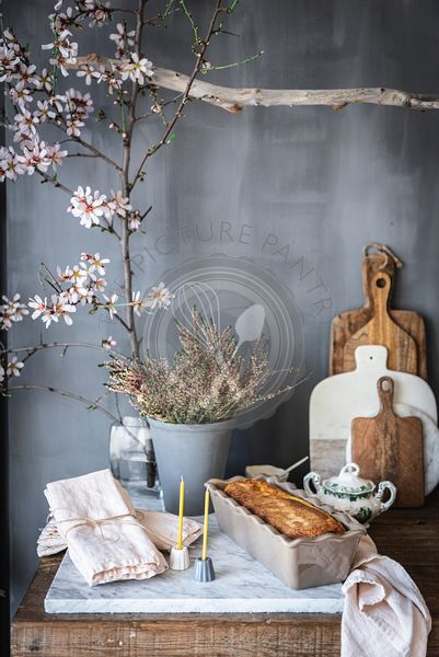 A cake in a tin on a marble counter in a rustic kitchen