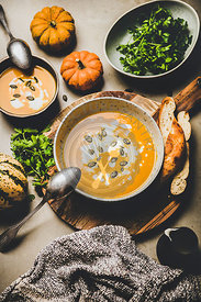 Flat-lay of pumpkin cream soup with seeds and fresh parsley