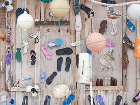 Plastic rubbish decorating wall picked up washed ashore on Wizard Island, Cosmoledo Atoll, Seychelles