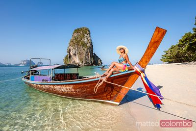 Beautiful woman sitting on longtail boat, Railay, Thailand