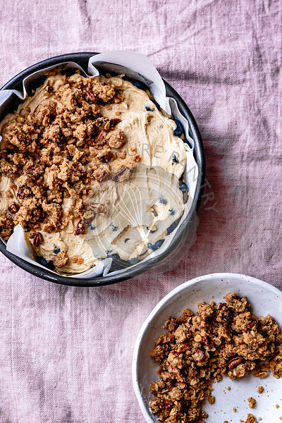 Pecan streusel scattered over blueberry coffee cake batter in a paper lined cake tin.