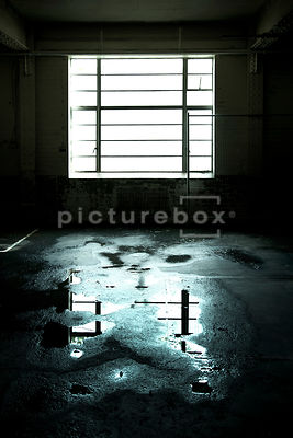 A window letting light into a damp and decaying room.