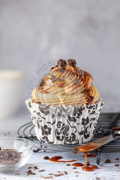 A coffee cupcake on a wire rack with caramel dripping off a knife alongside it