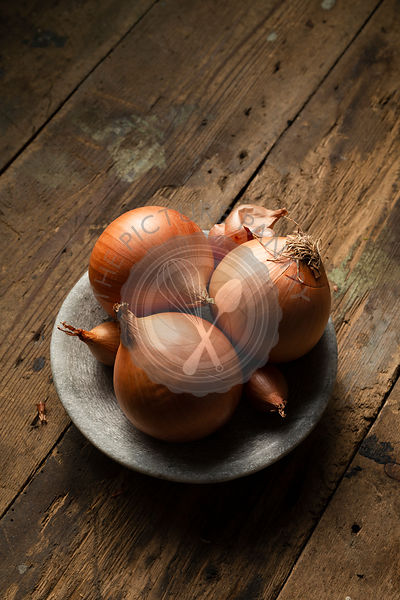 Brown onions and shallots in a stone bowl, on a rustic timber ba