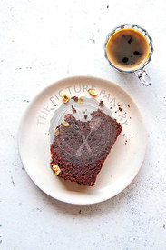 A slice of chocolate cake on a plate and a cup of coffee on the table