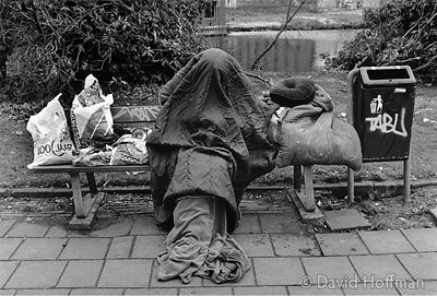 Unrecognisable homeless person with head covered by a sleeping bag sitting on a bench, Fleet Street, London, England.