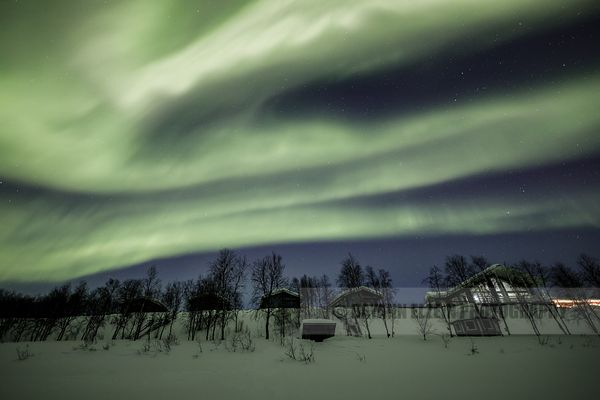 Strong northern lights above typical Finnish cottages in Utjsoki in Lapland