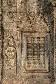 Bas relief sculpture, carvings on window and dancer at Ta Phrom temple. An UNESCO World Heritage. Siem Reap, Cambodia.