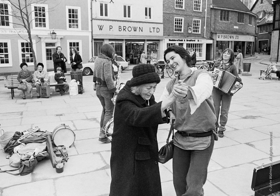 "#78605  Ros Davies dancing with ""Nellie"" while other members of The York Street Band play, York, March 1979.  Sarha Moore and..."