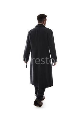 A semi-silhouette of a mystery man, with a gun, in a long black winter coat, walking away – shot from eye level.