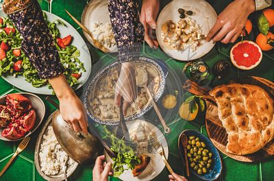 Flat-lay of people having Turkish dinner with lamb, rice, salad
