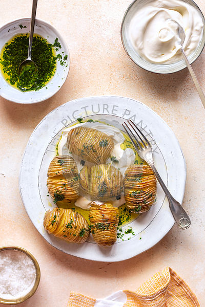 Roasted hasselback potatoes with parsely dressing on a plate.