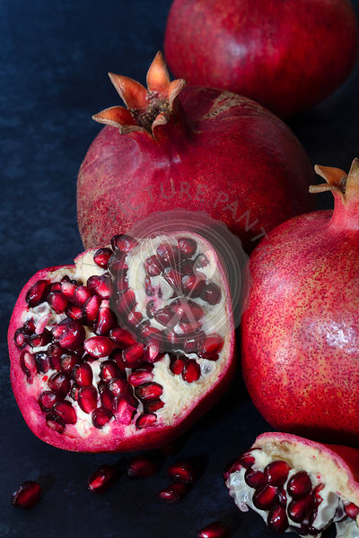 Red, ripe, juicy pomegranates against a dark blue background.