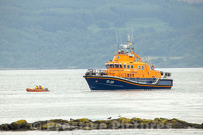 The Tobermory RNLI lifeboat and small inflatable searching in shallow water