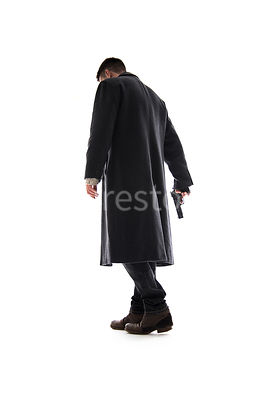 A Figurestock image of a mystery man, with a gun, in a long black winter coat, walking away – shot from low level.