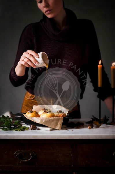 A woman preparing Baked Apples Stuffed with Granola and Dark Chocolate on a marble work surface