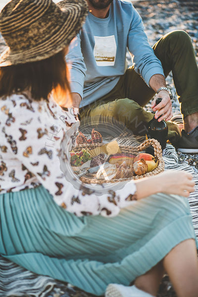 Young couple having picnic with sparkling wine, fruit and snacks