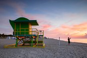 Teenager near lifeguard cabin at sunrise, Miami beach, USA