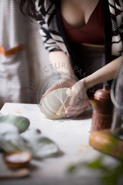 Young woman kneading bread