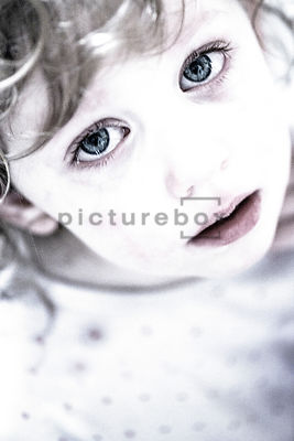 An image of a little girl with tears in her eyes, looking at camera.